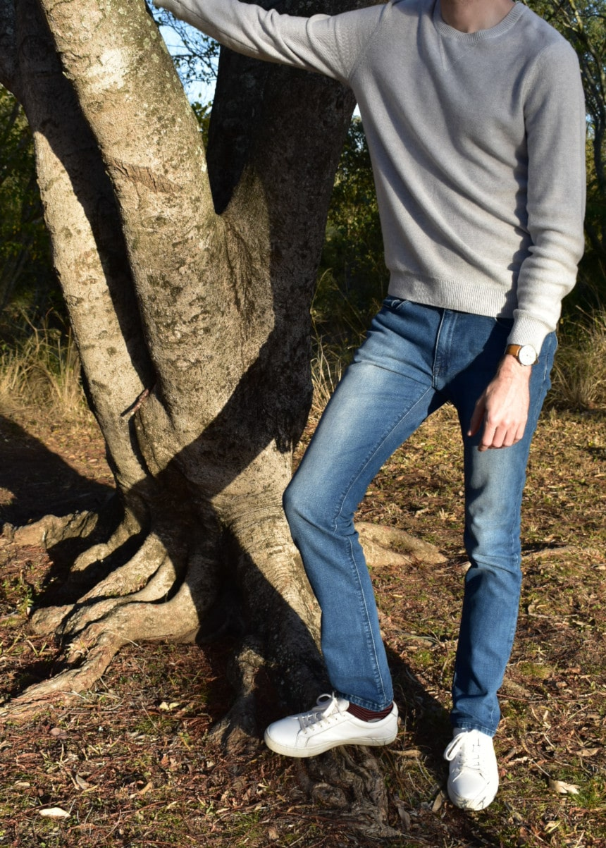 Model Wearing Mott & Bow Slim Laight Jeans with Liam Sweater Standing Up and Leaning On Tree with White Sneakers