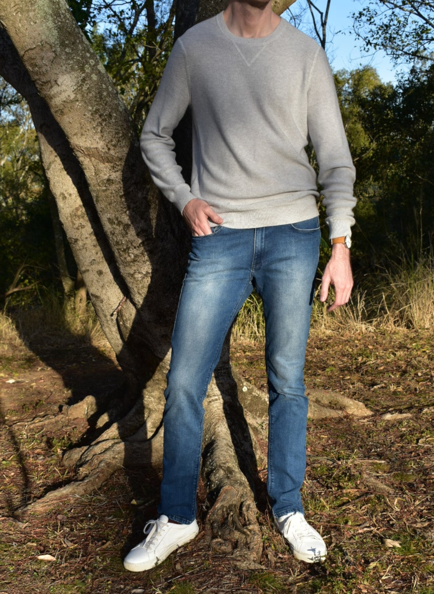 Model Wearing Mott & Bow Slim Laight Jeans with Liam Sweater Standing Up and Standing Next to Tree With Hand in Pocket and with White Sneakers
