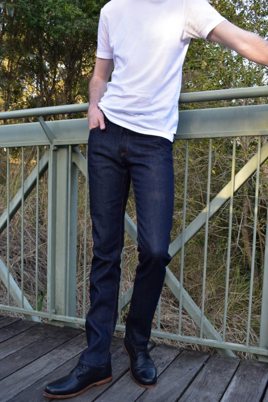Model Wearing Mott & Bow Slim Nofolk Raw Jean with White Shirt Standing on Bridge Hand in Pocket