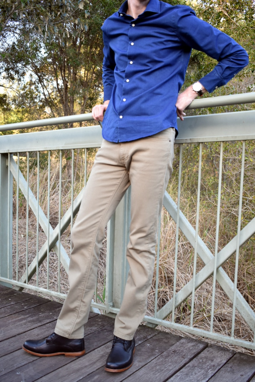 Model Wearing Mott and Bow Slim Mercer in Olive with Slim Semi Spread Wythe in Dark Blue and holding onto bridge railing