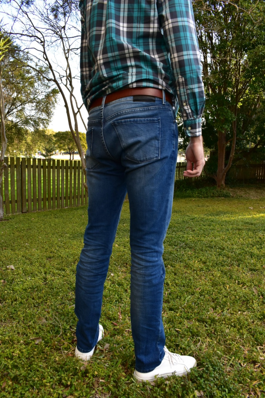 Picture of Model Wearing Mott & Bow Laight Jeans and a Flannel Shirt and White Sneakers While Standing in a Backyard