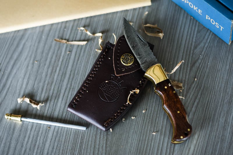 Bespoke Post Flip Review Knife Sitting on Top of Leather Pouch with Wood Shavings Around It