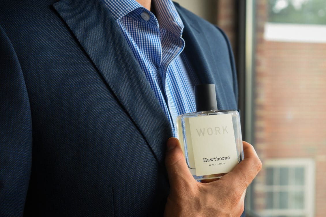 Male Model Wearing Blue Suit With Blue Check Shirt And Holding Hawthorne Work Fragrance Side Angle