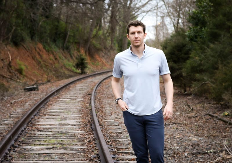 model wearing western rise limitless merino wool polo standing near train tracks