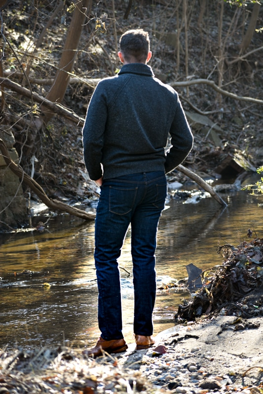 model at stream with shawl collar sweater and jeans