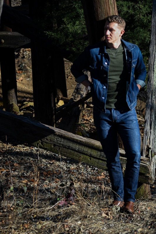 model in canadian tuxedo navy jeans with green sweater and denim jacket