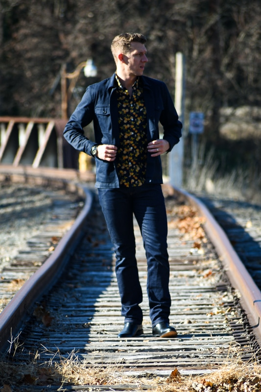 model on train tracks wearing navy and black outfit with dark blue jeans