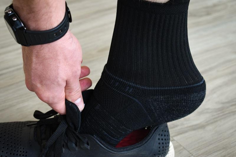 model putting on shoe wearing black strideline mid sock