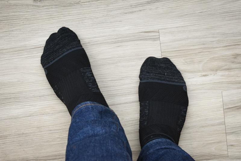 model standing with black crew strideline socks against wood background