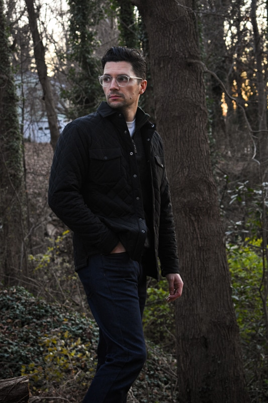model wearing sweater quilted jacket and dark blue jeans