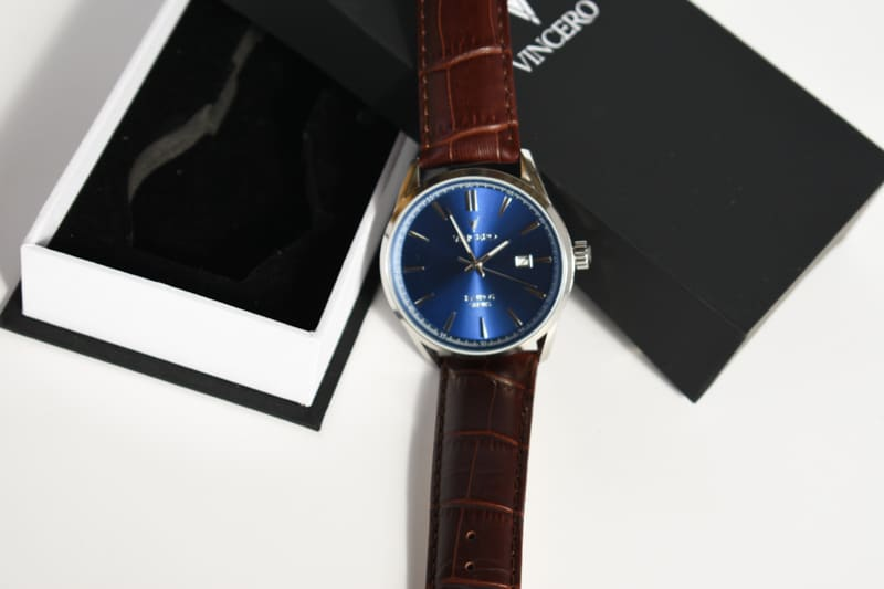 Vincero Kairos blue dial and brown strap lying on packaging