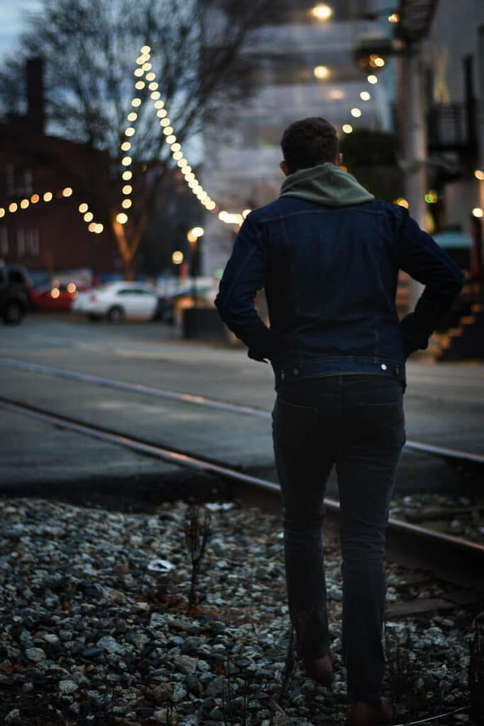 model facing away from camera walking train tracks dawn