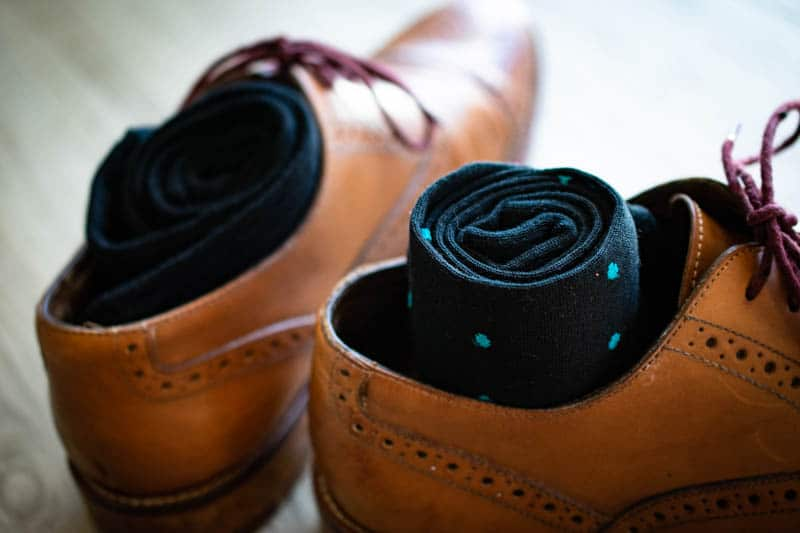 teal and navy polka dot sock rolled into leather oxford shoe