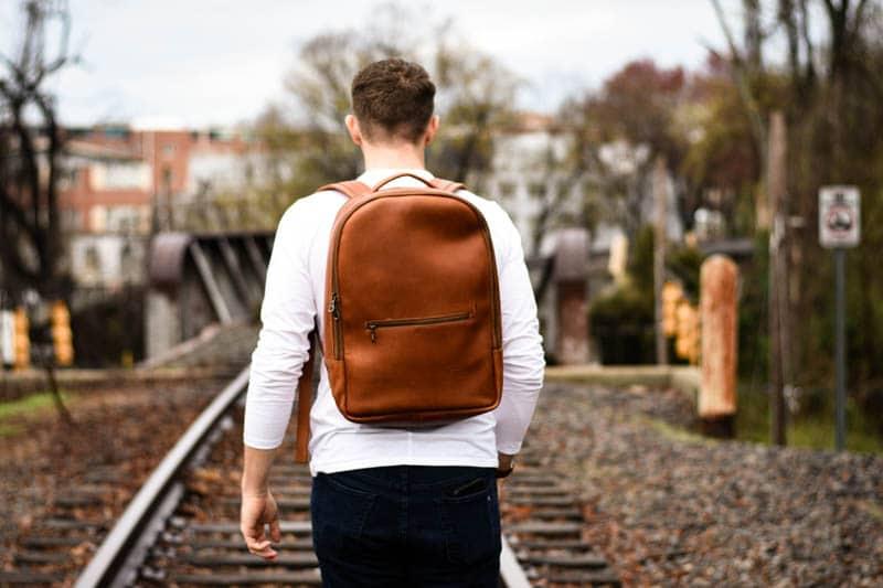 closeup model walking train tracks leather backpack tan