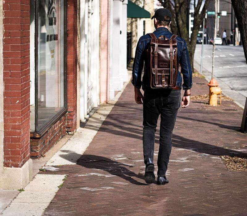 medium shot model wearing leather roll top backpack walking down sidewalk
