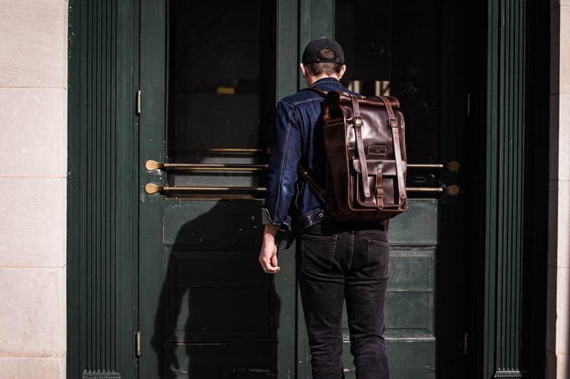 model entering large green doors wearing rolltop leather backpack moral code