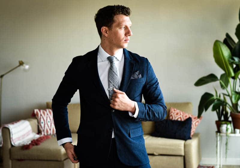 model looking to side wearing navy suit and gentlemens box accessories