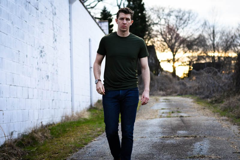 model wearing green tshirt and jeans walking against white wall