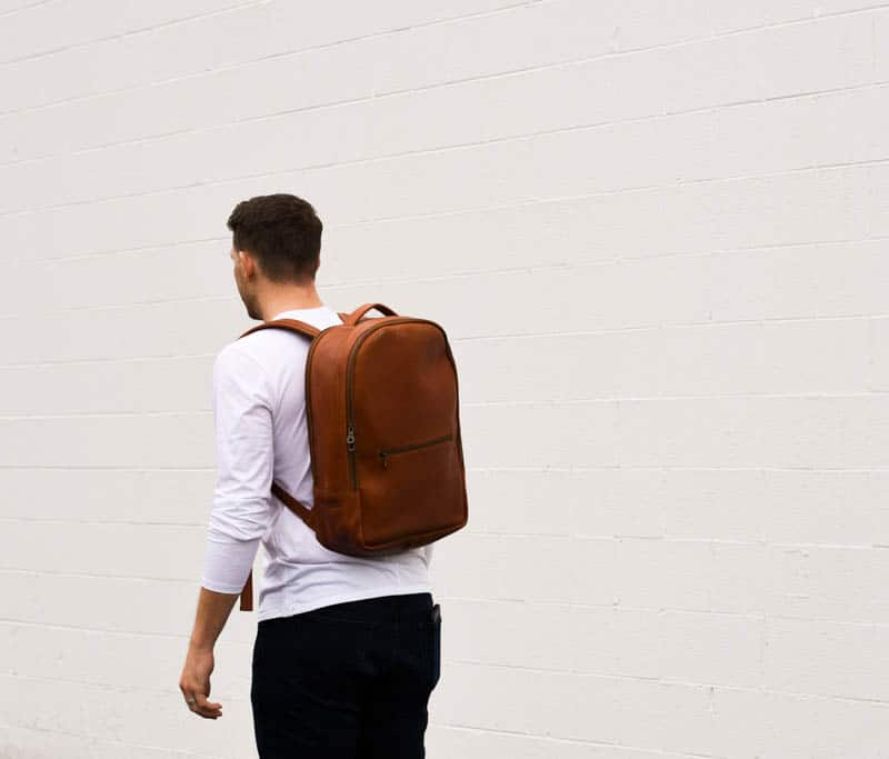 model wearing parker clay atlas leather backpack against white wall