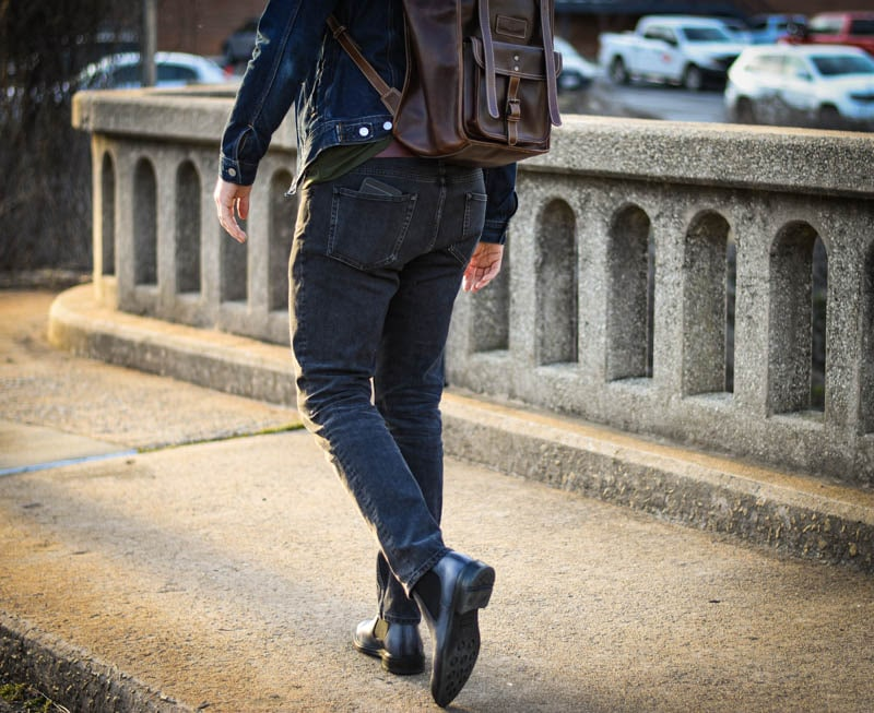 model with leather rolltop backpack and ice blue lawry chelsea boots from Moral Code