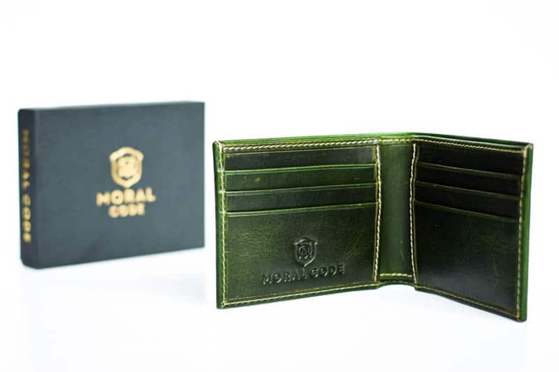 opened moral code green leather wallet on white background with product box