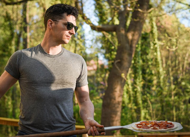 model holding pizza while wearing university heights sunglasses