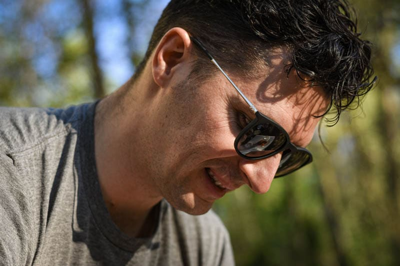 model smiling and looking down wearing university heights sunglasses