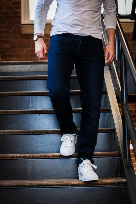 model walking down stairs with jeans and rb1 low rag and bone white minimalist sneakers