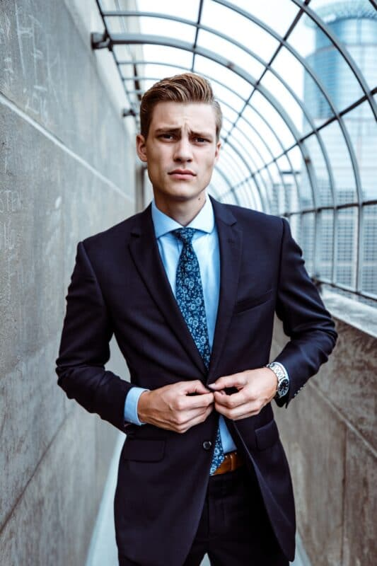 model wearing navy suit and light blue shirt with floral tie