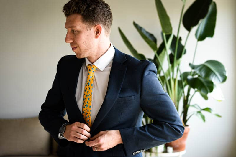 model wearing navy suit white shirt and yellow floral tie