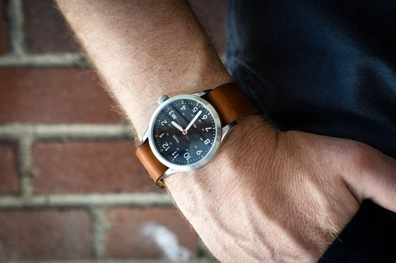 model wearing vaer c5 black heritage field watch with leather single pass horween strap