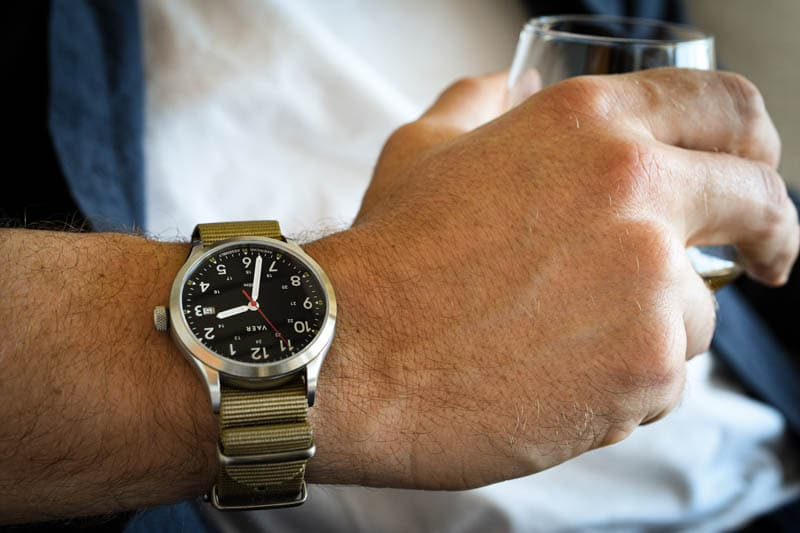 model wearing vaer c5 heritage field watch holding glass