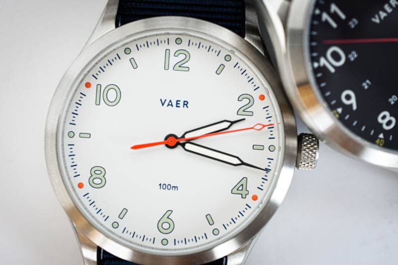 vaer s5 field watch leaned next to c5 black field watch with white background