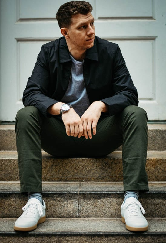 model sitting on concrete step wearing minimalist outfit from asket