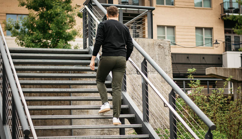 model walking up steel steps with olive asket chinos