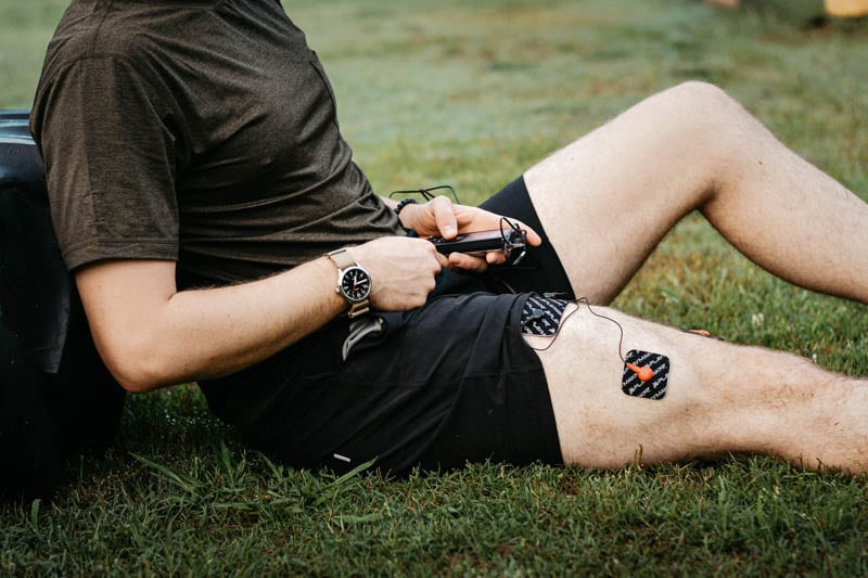 Athlete using wired electric muscle stimulator on leg