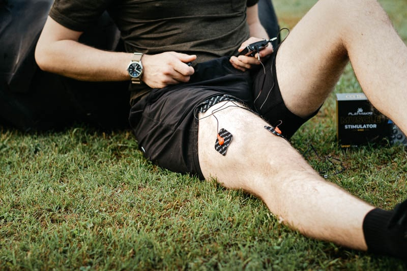 athlete using wired muscle stimulator on quadricep